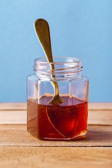 Pot de miel avec une cuillère vue de face