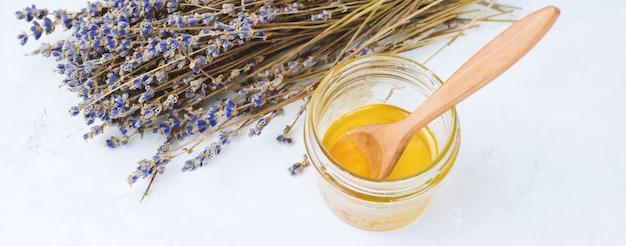 Pot de miel et fleurs de lavande séchées sur un béton minable blanc