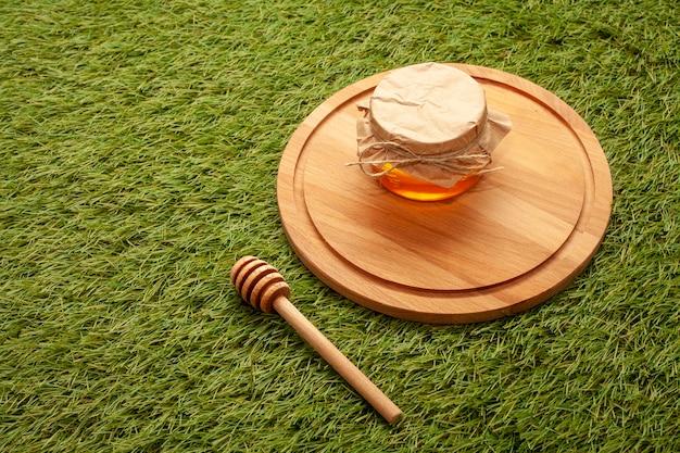 Pot de miel gros plan sur une planche de bois