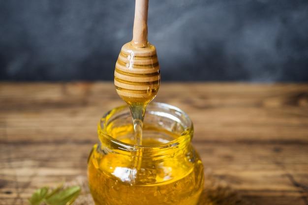 Un pot de miel liquide de fleurs de tilleul et un bâton avec du miel sur une surface sombre. espace de copie