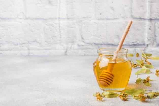 Pot de miel liquide à partir de fleurs de tilleul et d'un bâton sur une surface de béton grise. espace de copie.