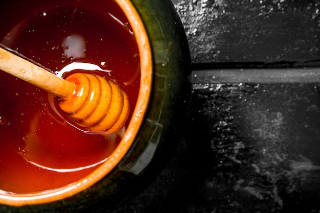Pot de miel naturel. sur une surface rustique noire.