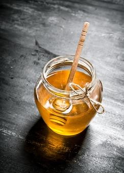 Pot de miel naturel. sur la table rustique noire.