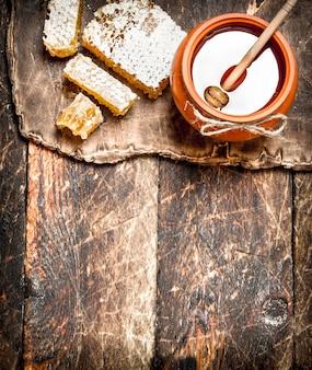 Pot de miel et nid d'abeille avec une cuillère en bois. sur fond de bois.