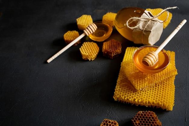 Pot de miel avec nid d'abeille sur table noire