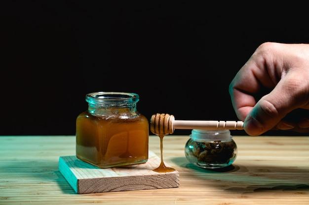 Pot de miel de noisette sur une surface en bois et un mur noir et une main tenant une cuillère à miel avec du miel dessus