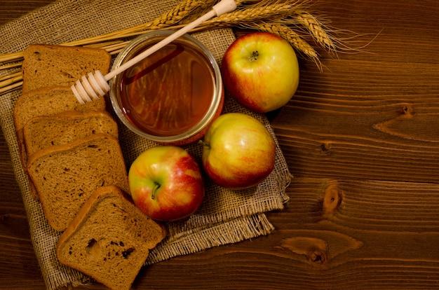 Pot de miel, pommes, pain de seigle, oreilles sur le sac, table en bois, vue de dessus