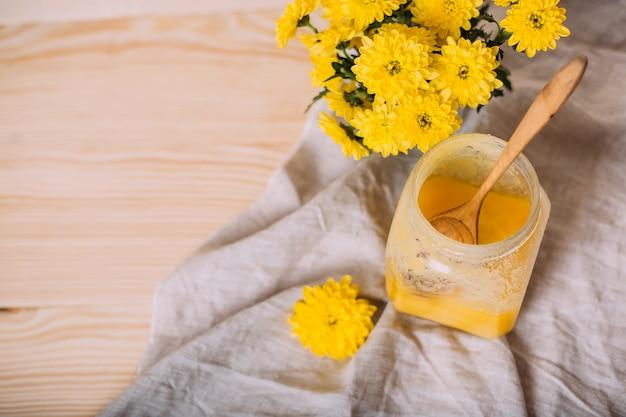 Un pot de miel solide et de fleurs sur une table en bois.