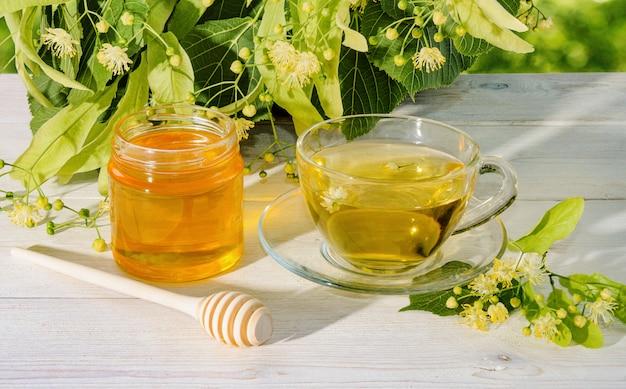 Pot de miel de tilleul, chapeau de thé de tilleul et branche avec des fleurs de tilleul sur une journée ensoleillée