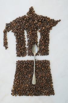 Pot de moka fait de grains de café fraîchement torréfiés sur un fond de marbre avec une cuillère à thé. modèle de café.