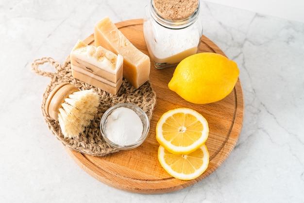 Pot de nettoyants naturels écologiques avec du bicarbonate de soude brosse à vaisselle savon au citron sur une table en marbre blanc