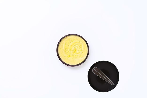 Un pot noir avec de la crème jaune avec de l'huile d'argousier à côté de laquelle se trouve un couvercle avec une spatule sur un fond blanc