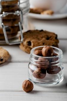 Pot avec des noix et de délicieux cookies sur table