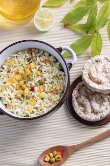 Un pot de nouilles savoureuses avec du maïs, des pois et des croûtes de pain rondes