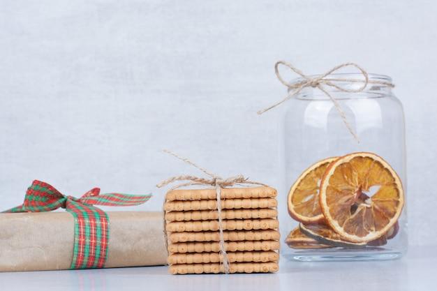 Pot d'orange séchée et biscuits sur fond de marbre.
