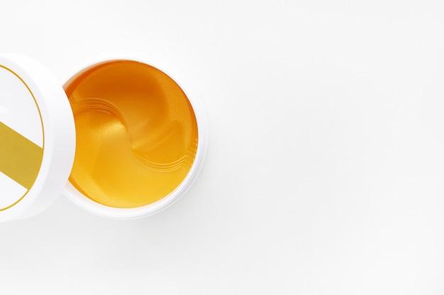 Pot ouvert avec des patchs d'hydrogel pour les yeux. cache œil hydrogel à énergie dorée. vue de dessus avec espace de copie.