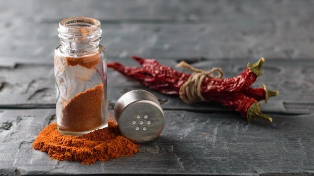 Un pot ouvert de poudre de poivron rouge sur une table en bois foncé