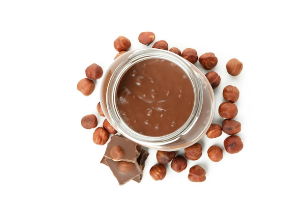 Pot avec de la pâte de chocolat et des noix isolé sur fond blanc