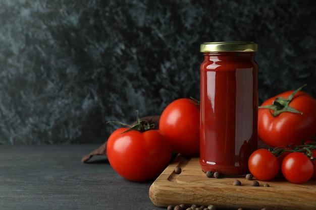 Pot avec pâte de tomates et tomates sur table en bois