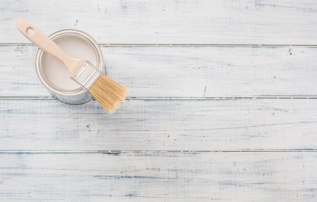 Pot de peinture de dessus de couleur blanche et pinceau sur table.