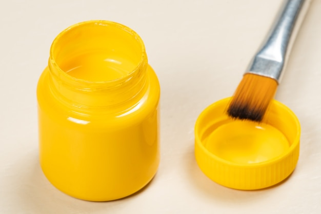 Pot de peinture à la gouache ouverte avec le couvercle sur le côté