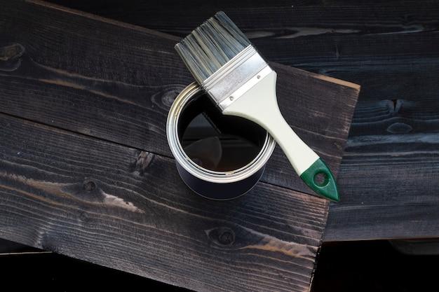 Pot de peinture et pinceau sur un bureau en bois foncé