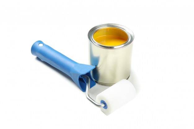 Pot de peinture et rouleau isolé sur une surface blanche