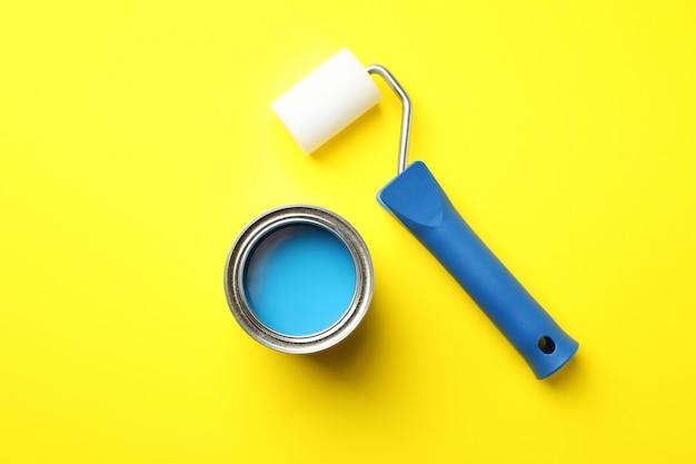 Pot de peinture et rouleau sur surface jaune