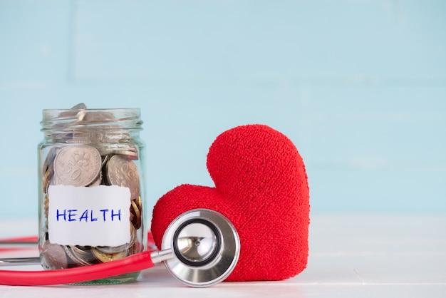 Un pot de pièces de monnaie avec stéthoscope et coeur rouge sur fond de bois.