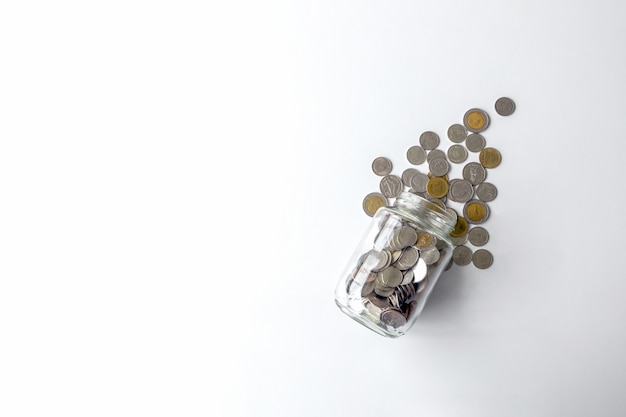 Pot avec des pièces de monnaie thaïlandaises sur la table