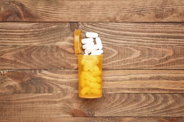 Pot avec des pilules sur fond de bois