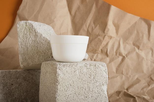 Pot en plastique blanc pour crème ou gommage sur podium en béton sur fond marron