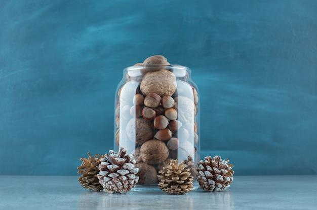 Un pot plein de noix à côté de pommes de pin sur une surface en marbre