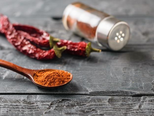 Un pot de poivre, trois gousses et une cuillère de piment moulu sur une table rustique
