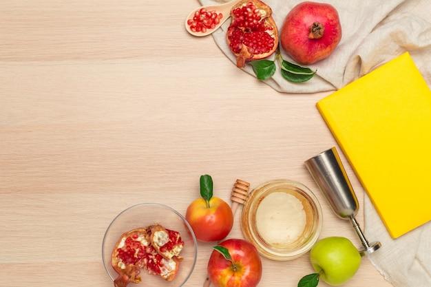 Pot de pomme rouge, de grenade et de miel pour le nouvel an juif sur une planche de bois