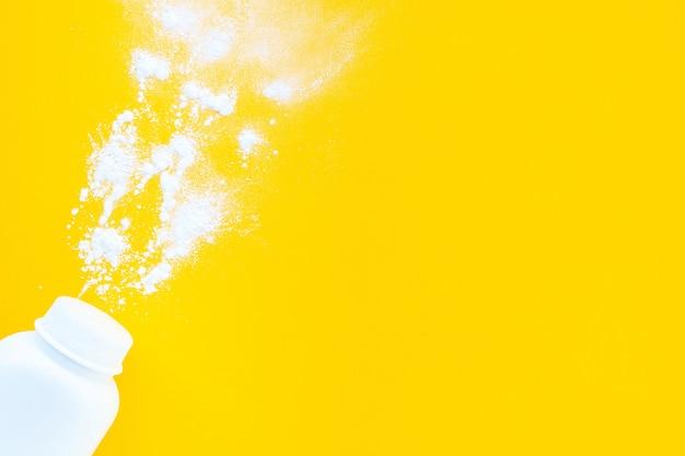 Pot de poudre pour bébé blanc sur fond jaune, mise en page à plat, vue de dessus, espace de copie, maquette. concept minimaliste d'hygiène de bébé.