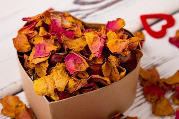 Pot-pourri et châtaignes en boîte coeur près de boîte avec arôme de pot-pourri de romance