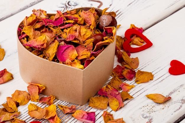 Pot-pourri et châtaignes près de coeurs pétales séchés dans une boîte en forme de coeur cadeau naturel en vacances