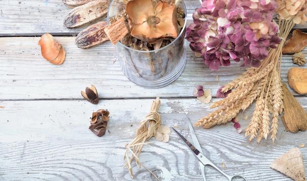 Pot-pourri dans un bocal en verre et fleurs sèches sur une table en bois blanc