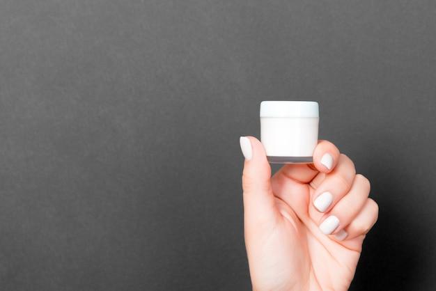 Un pot de produit cosmétique dans une main féminine au noir