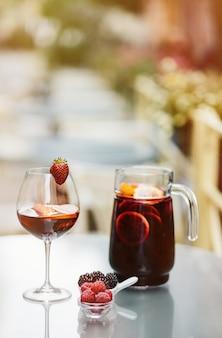 Pot de sangria et verre aux fruits rouges