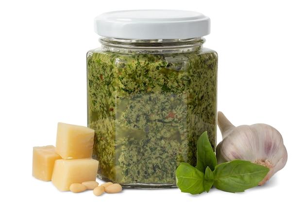 Pot de sauce pesto italienne et ingrédients isolés sur fond blanc