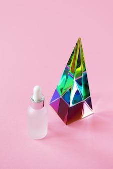 Pot de sérum avec maquette de pipette et prisme pyramidal en verre sur rose