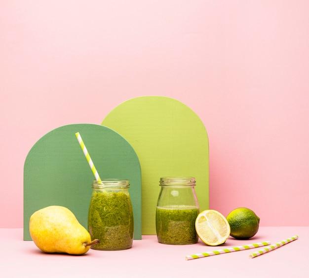 Pot avec smoothie frais de poire et citron vert sur table