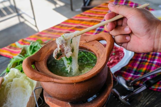 Pot en terre cuite thaïlandais traditionnel shabu shabu épicé, trempant la viande dans une soupe épicée bouillie.
