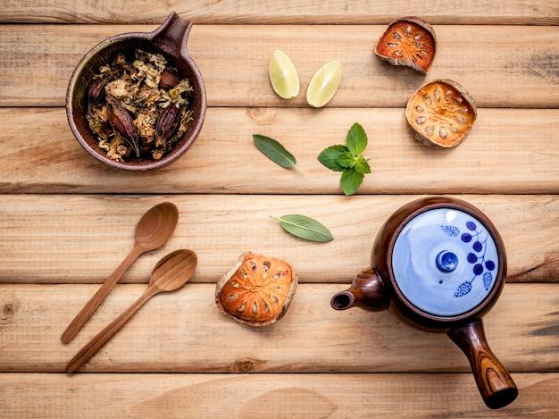 Pot de thé à base de plantes avec des herbes fraîches sur fond en bois rustique.