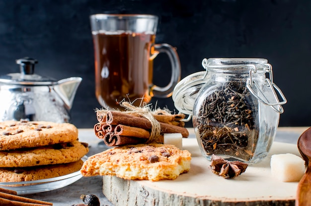 Pot à thé, biscuits maison et épices à thé sur fond sombre,