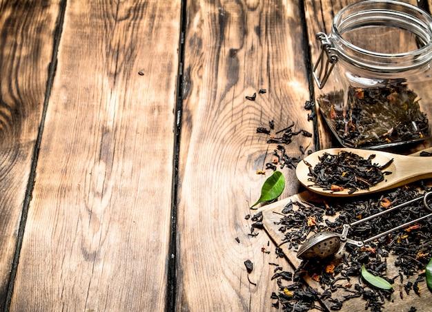Pot de thé séché avec une cuillère à thé et des feuilles vertes. sur table en bois.