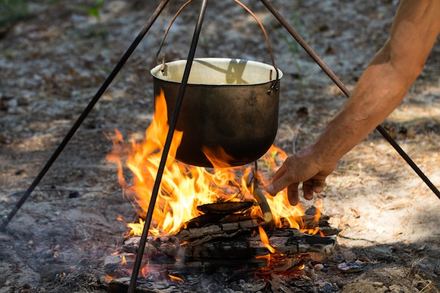 Pot touristique suspendu au-dessus du feu sur un trépied. cuisine à la campagne.