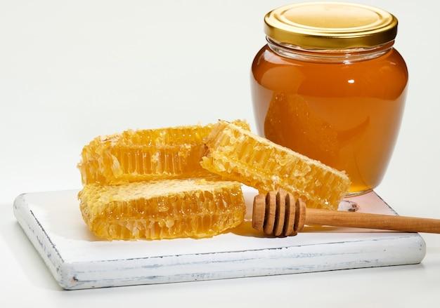 Pot transparent en verre avec du miel et des morceaux de nid d'abeilles en cire avec du miel sur une planche en bois blanche, fond blanc